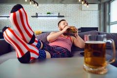 Engra?ado grosso antrop?fago um hamburguer que senta-se no sof? foto de stock
