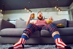 Engra?ado grosso antrop?fago um hamburguer que senta-se no sof? imagem de stock