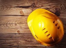Engranaje amarillo del casco de seguridad en la tabla de madera Foto de archivo libre de regalías