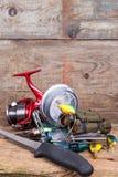 Engranaje de la pesca y del turismo en tablero de la madera Imagen de archivo