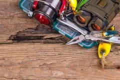 Engranaje de la pesca y del turismo en tablero de la madera Foto de archivo libre de regalías
