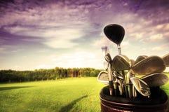 Engranaje del golf, clubs en la puesta del sol Fotografía de archivo