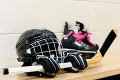 Engranaje del hockey del ` s de la muchacha: casco, guantes, palillos, patines con los cordones rosados fotografía de archivo