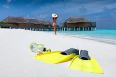Engranaje que bucea en una playa tropical con la mujer que camina en la playa fotografía de archivo