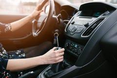 Engranajes cambiantes de la mujer joven en coche Conducción de una opinión de Car imagenes de archivo