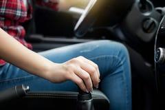 Engranajes de desplazamiento de la mujer en el coche Fotos de archivo