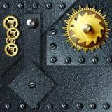Engranajes del oro contra el metal ferroso Fotos de archivo