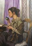 Engrase en lona de una mujer que bebe mientras que lee su libro Fotos de archivo libres de regalías