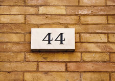Engraved building number. Of fourty four on old, brown brick wall in Rome Royalty Free Stock Photography
