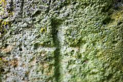 Engraved cross on the old stone surface. Close up Royalty Free Stock Images