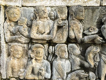 Engraved figures depicts the story of Buddha on a stone wall of Borobudur, Indonesia Royalty Free Stock Image