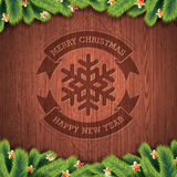 Engraved Merry Christmas and Happy New Year typographic design with fir tree on wood texture background. Royalty Free Stock Photography