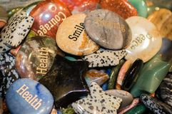 Engraved rocks that show words of wisdom and encouragement. Engraved rocks that show words of wisdom and encouragement in a shiny pile royalty free stock photos