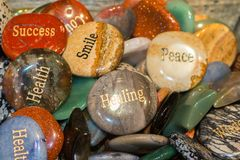 Engraved rocks that show words of wisdom and encouragement. Engraved rocks that show words of wisdom and encouragement in a shiny pile stock photography