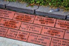 Engraved veteran memory bricks in Sedalia. SEDALIA, MO, USA - AUGUST 3, 2015: Engraved veteran memory bricks in sidewalk pavement surrounding Pettis County Stock Images