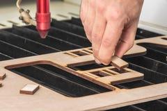 Engraver лазера работая и гравируя деревянная доска с рукой стоковая фотография
