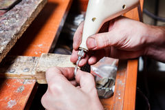 Engraving. Jeweler's hands engraving on the ring stock image