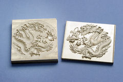 Engraving dragon. Two pieces of engraving dragon plate isolated on blue stock photography