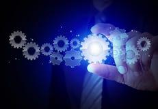 Engrenagem da mostra da mão do homem de negócios ao sucesso como o conceito Imagem de Stock