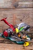 Engrenagem da pesca e do turismo na placa da madeira Fotos de Stock