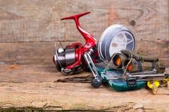 Engrenagem da pesca e do turismo na placa da madeira Foto de Stock