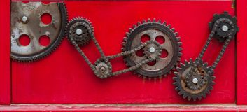 Engrenagem de corrente oxidada velha em um backgro vermelho fotos de stock