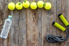 Engrenagem do esporte Bolas de tênis e corda de salto no copyspace de madeira da opinião superior do fundo Foto de Stock