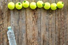 Engrenagem do esporte Bolas e água de tênis no copyspace de madeira da opinião superior do fundo Foto de Stock