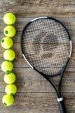 Engrenagem do esporte Bolas e raquete de tênis na opinião superior do fundo de madeira Fotografia de Stock