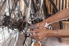Engrenagem velha da bicicleta da manutenção diy da mão que stering Fotografia de Stock Royalty Free
