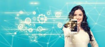 Engrenagens com a jovem mulher que guarda para fora um smartphone imagem de stock royalty free