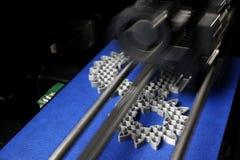 Engrenagens de dente reto da fabricação de FDM 3D-printer do filamento prata-cinzento na fita da cópia azul Fotografia de Stock Royalty Free