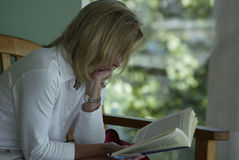 Engrossed. Woman engrossed in reading a book Royalty Free Stock Photo