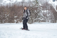 An engrossed female snowboarder is skiing with her snowboard Royalty Free Stock Photos