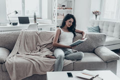 Engrossed in good book. Beautiful young woman reading a book while sitting on sofa at home Royalty Free Stock Photo