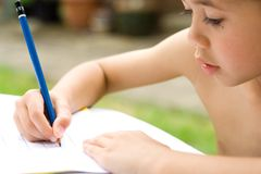 Engrossed in his writing. Young boy engrossed in his writing homework , an outdoor setting Royalty Free Stock Photo