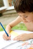 Engrossed in his writing. Young boy engrossed in his writing homework , an outdoor setting Stock Photo