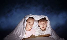 Engrossed little girl and boy reading book stock photos