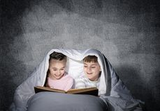 Engrossed little girl and boy reading book royalty free stock images