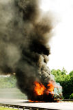 Engulfed by fire. Truck in fire with black smoke on the road Stock Images