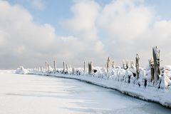 Old breakwater covered in snow. Engure, Latvia. Old Engure port breakwater covered in snow and ice on cloudy sky background Royalty Free Stock Photo