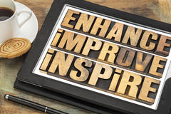 Enhance, improve, inspire word abstract. A collage of motivational words in vintage letterpress wood type on a digital tablet with a cup of coffee royalty free stock photo