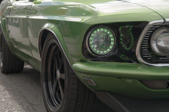 Enhanced Headlights on Classic Car. A green classic car with green lined headlights at the Muscle and Chrome Car Show in Seaside, OR, USA Stock Photo