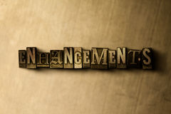 ENHANCEMENTS - close-up of grungy vintage typeset word on metal backdrop Stock Photography