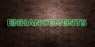 ENHANCEMENTS - fluorescent Neon tube Sign on brickwork - Front view - 3D rendered royalty free stock picture Stock Photos