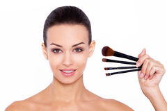 Enhancing the beauty already there. Closeup of a gorgeous young woman holding cosmetic brushes near her face on a white background Royalty Free Stock Images