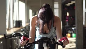 Attractive woman enhancing her endurance while working out on an exercycle. Enhancing her endurance while working out on an exercycle stock footage