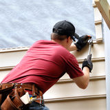 Enhancing his new home. First time home buyer works to install siding on his new home.  He is hammering into place a sheet of siding.  He has on a red shirt and Stock Image