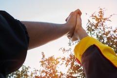Enhet och teamworkbegrepp: Gjort suddig av gruppstudenthänder tillsammans i utomhus- klassrum för aktiviteter Sikt av asiatiskt b royaltyfria foton