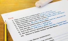 Enhglish test sheet. English test sheet on wooden table with stationery Royalty Free Stock Photo